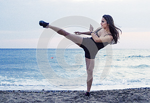 Powerful woman performing martial arts kick