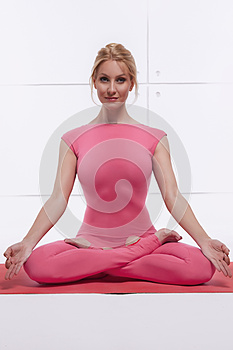 Beautiful attractive blond woman doing yoga sitting in the lotus position relaxes and opens chakras dressed in comfortabl
