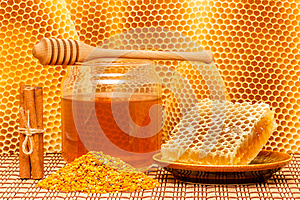 Honey in jar with dipper, honeycomb, pollen and ci