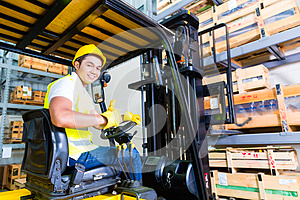 Asian fork lift truck driver lifting pallet in storage