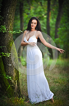 Lovely young lady wearing an elegant long white dress enjoying the beams of celestial light on her face in enchanted woods. Long