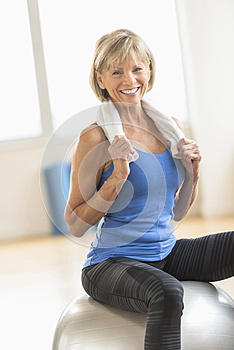 Woman With Towel Around Neck Sitting On Fitness Ball