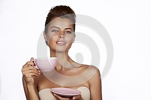 Young sexy beautiful woman with dark hair picked up holding a ceramic cup and saucer pale pink drink tea or coffee on a white back
