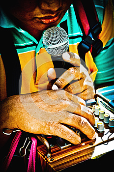 Blind beggar hold the microphone to sing. Bangkok, Thailand