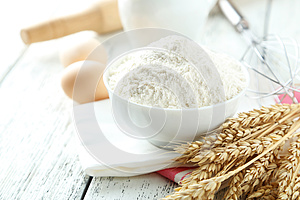Bowl of wheat flour with eggs and whisk on white wooden backgrou