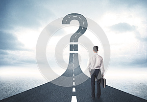Business person lokking at road with question mark sign