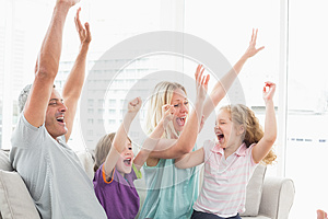 Family celebrating success while watching TV
