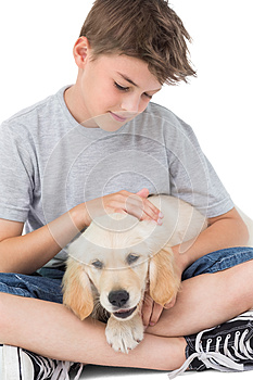 Boy stroking dog over white background