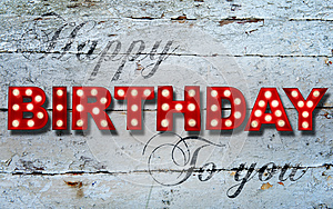 Glowing Happy Birthday on wooden background