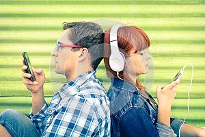 Hipster couple in disinterest moment with mobile smart phones
