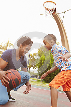 Father With Son Playing Basketball In Park Together
