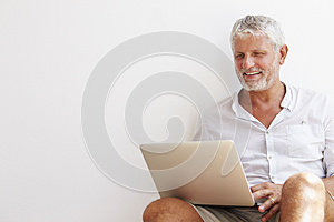 Mature Man Sitting Against Wall Using Laptop