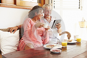 Mature Couple Sitting At Breakfast Table With Digital Tablet