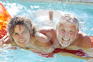 Mature Couple Relaxing On Airbed In Swimming Pool