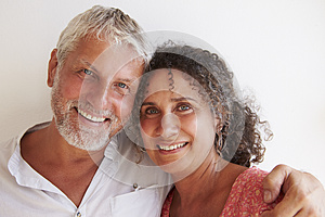 Portrait Of Loving Mature Couple Standing Against Wall