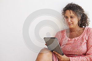 Mature Woman Sitting Against Wall Using Digital Tablet