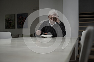 Retired man eating soup