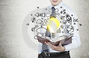 Businessman is holding a book with flying around business icons and a light bulb as a concept of the new business ideas.