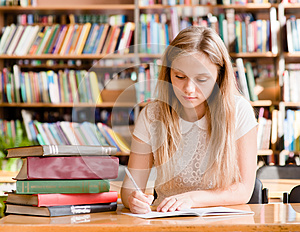 Pretty female student with books working in a high school library