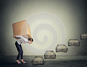 Difficult task concept. Woman carrying heavy box upstairs