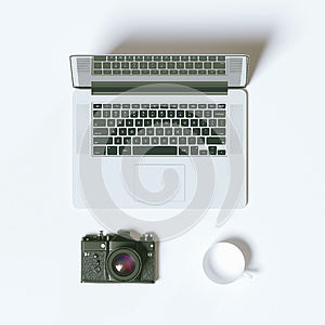Top view laptop photo camera and coffee cup