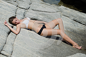 Woman is lying down and sunbathing on solid rocks