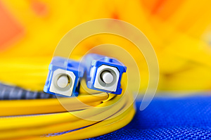 Fiber optic connectors close up on a colourful background.