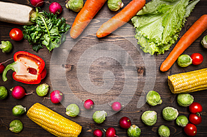 Healthy foods, cooking and vegetarian concept peppers, carrots, daikon, lettuce, radishes, corn, rosemary place text,frame on