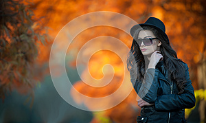 Beautiful woman with black hat and sunglasses posing in autumnal park. Young brunette spending time during autumn in forest