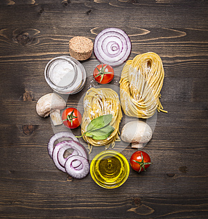 Pasta with fresh vegetables , preparation with flour on rustic wooden background, top view. Vegetarian food healthily cooking