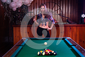Young woman posing in front of billiard pool table
