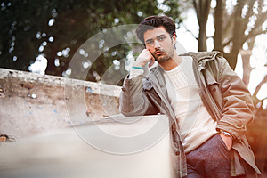 Handsome young bored man leaning on a wall. Outdoor