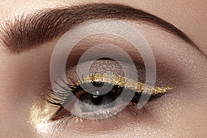 Beautiful macro shot of female eye with ceremonial makeup. Perfect shape of eyebrows, eyeliner and pretty gold line on eyelid