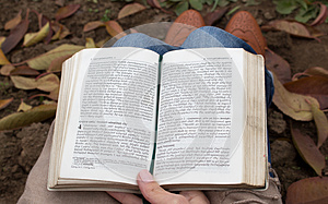 Person sitting on the ground reading a book(Bible)