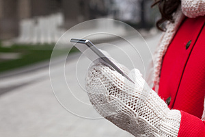 Woman in red coat with smartphone in hands going through the cit