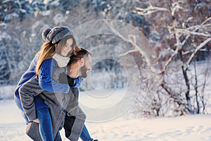 Happy loving couple walking in snowy winter forest, spending christmas vacation together. Outdoor seasonal activities.