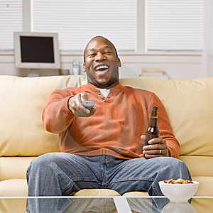 Man holding remote control watching television