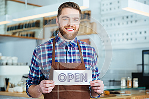 Happy attactive young barista holding open sign at coffee shop