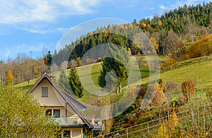 Landscape autumn countryside with wooden farmhouses on green hill and mountains in the background,Germany