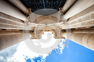 Arch and columns with capitals. Blue sky and clouds
