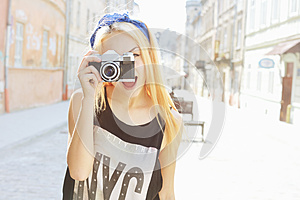 Outdoor summer smiling lifestyle portrait of pretty young woman having fun in the city in Europe with camera. Travel photo of phot