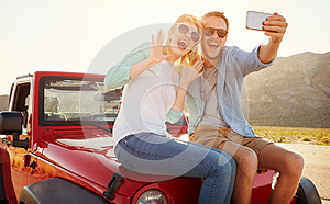Couple On Road Trip Sit On Convertible Car Taking Selfie