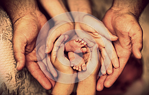 Hands of father, mother, daughter keep little feet baby. Friendly happy family