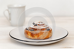 Cinnamon roll with raisins in a ceramic saucer