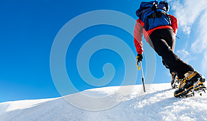 A climber reaches the top of a snowy mountain. Concept: courage, success, perseverance, effort, self-realization.