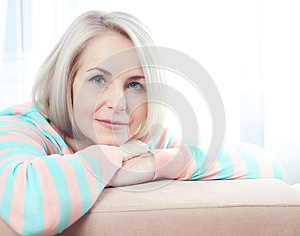 Active beautiful middle-aged woman smiling friendly and looking into the camera at home. Woman's face close up.