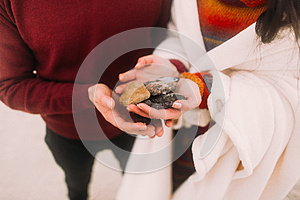 Colorful sea pebbles on couple's hands close up. Happy young couple at the winter beach wrapped in white blanket