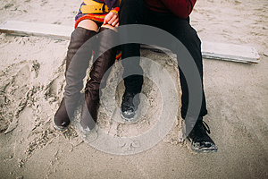 Couple sitting on the sand at winter beach. Half-length portrait. Couple's legs in hipster shoes close up