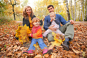 Family of four with yellow leaves sits in wood