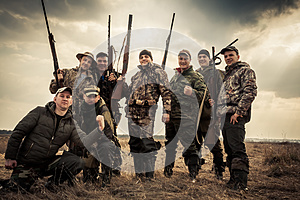 Hunters standing together against sunrise sky in rural field during hunting season. Concept for teamwork